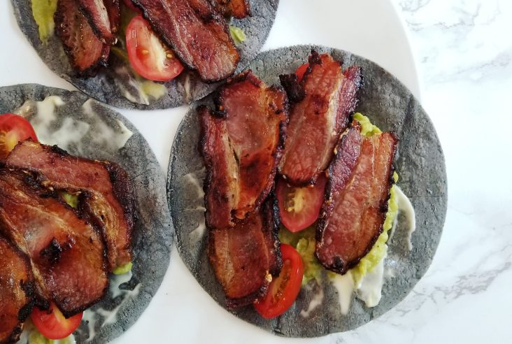 An overhead shot on a white marble background. A white plate with three blue-corn tortillas featuring homemade mayonnaise, tomatoes, and pieces of bacon.