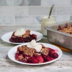A slice of berry crumble on two small white plates. The pan it was baked in is on the right and behind that is a small glass jar with a mix of coconut milk yogurt and honey with a spoon sticking out of it