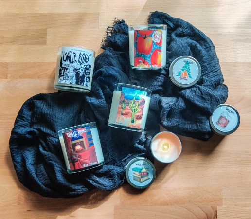 An assortment of Uncle Ron's candles arranged with a black scarf on a wooden table. A mini candle is lit and burning.