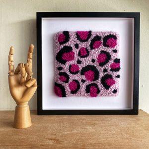 Pink leopard print framed wall art on a shelf beside a hand shaped ornament