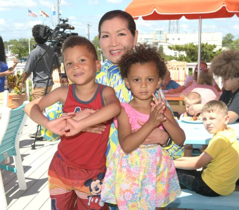 Yumi Hogan with children at the children's house by the sea
