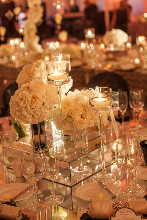 white rose centerpiece surrounded by candlelight