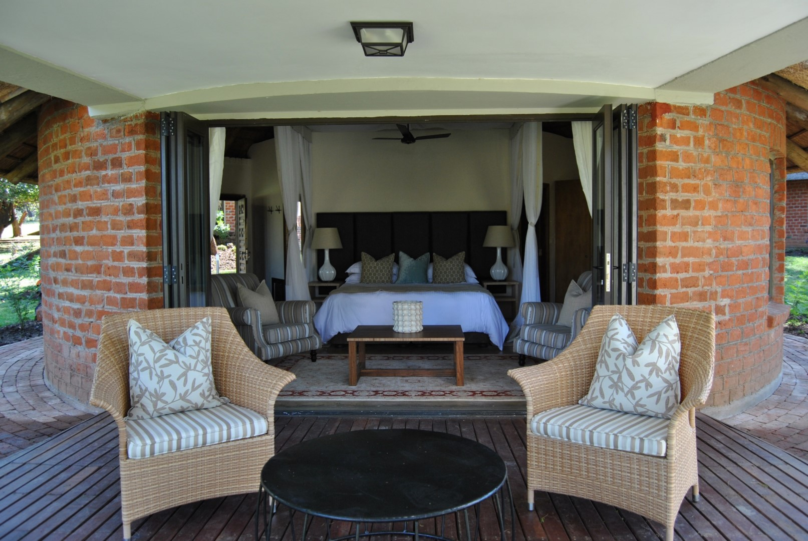 Two Makuti arm chairs in honey wicker