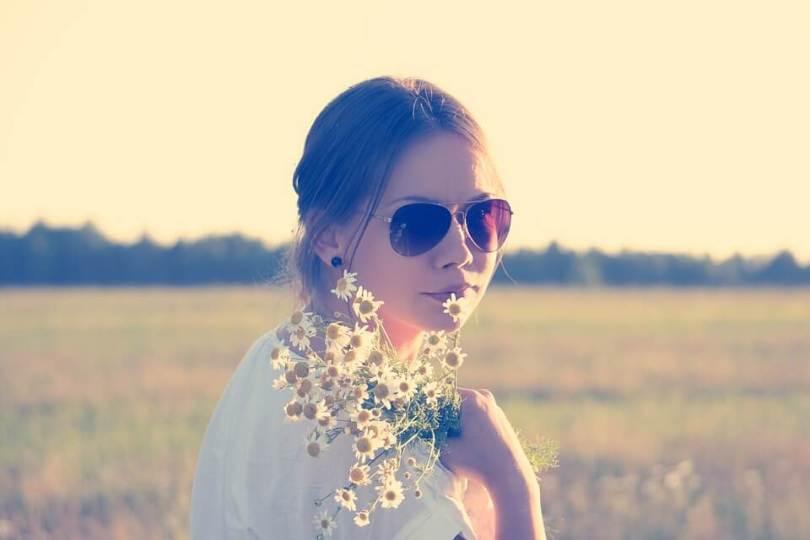 napszemüveges lány a réten virágokkal a kezében