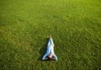 zöld füvön heverő fitalal lány