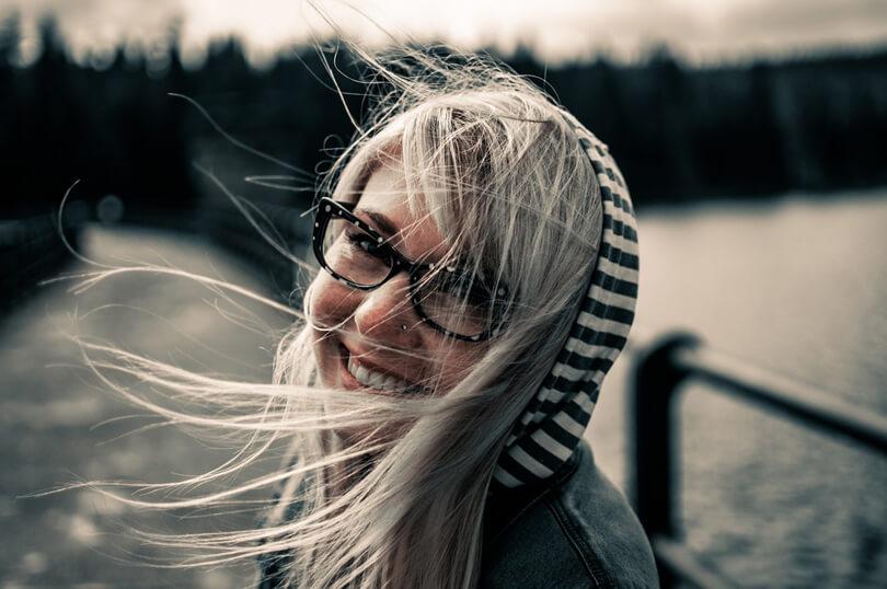 szemüveges mosolygós lány szélben
