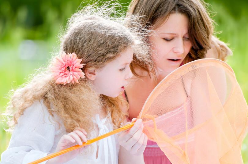 anya lánya csodálkozva néz bele egy lepkehálóba