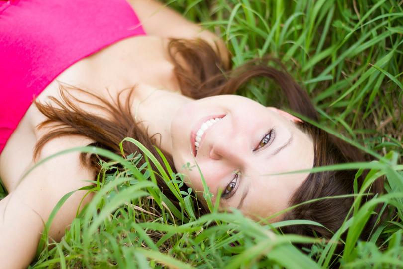 mosolygós lány fekszik a fűben