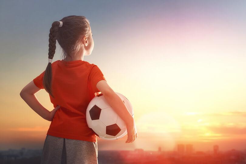 lány a hóna alatt focilabdával