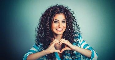 göndörhajú lány szívet formál a kezeivel