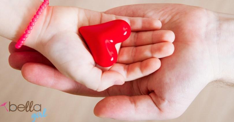 férfi kézben egy lány keze, abban egy piros szív