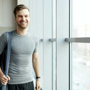 Cheerful man with yoga mat bag