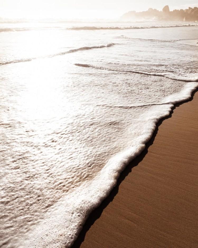 white wave, sandy beach, sunlit