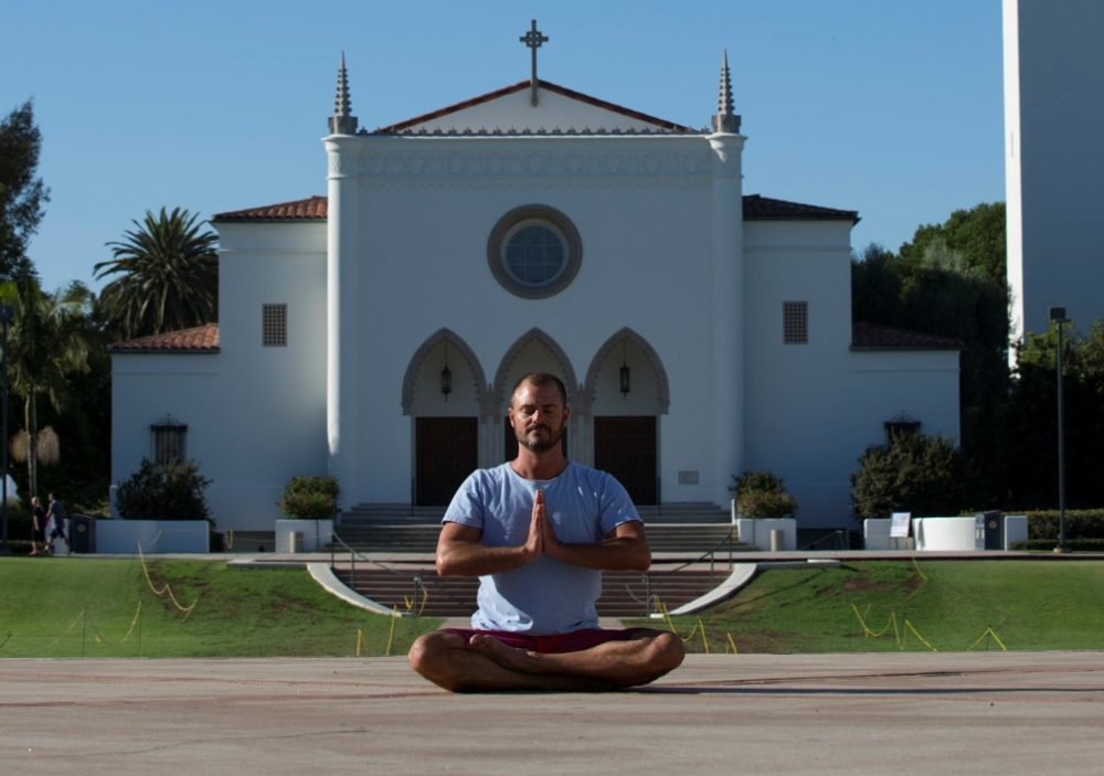 Alumni Andre meditating in front of LMU Chapel