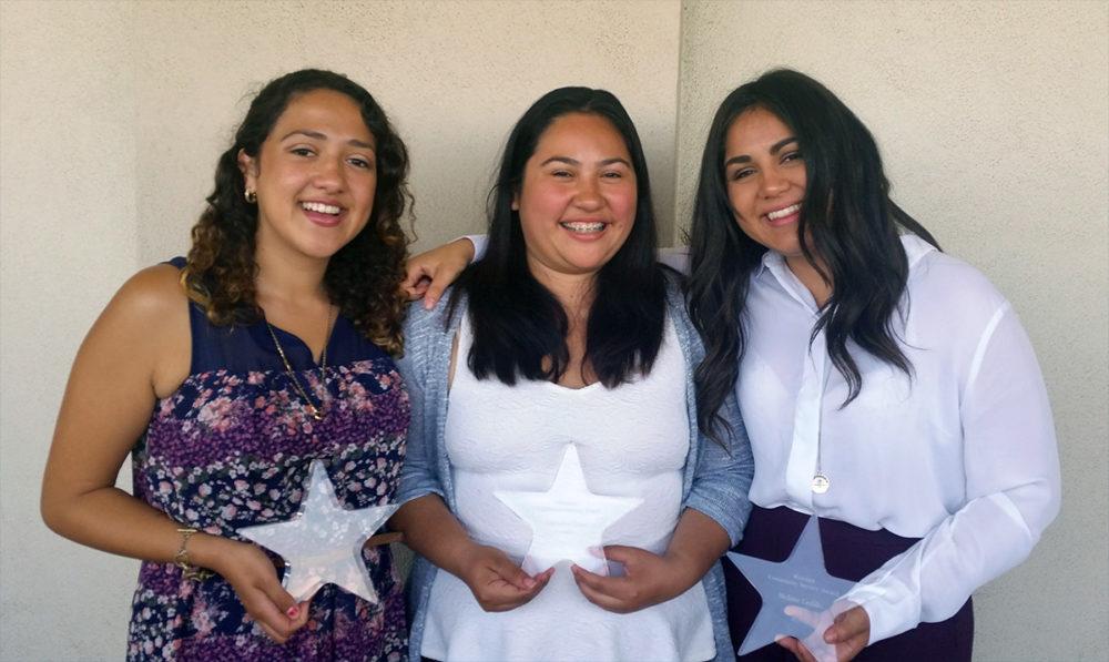 3 students holding the Riordan Awards