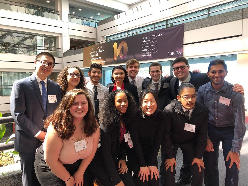 BCLA students in front of a poster for the 10th Undergraduate Research Symposium in UHall