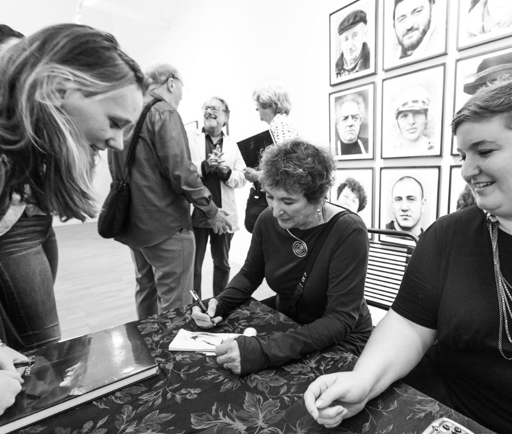 "Black and white shot of Judy Dater signing autographs at ""Only Human"" exhibit"