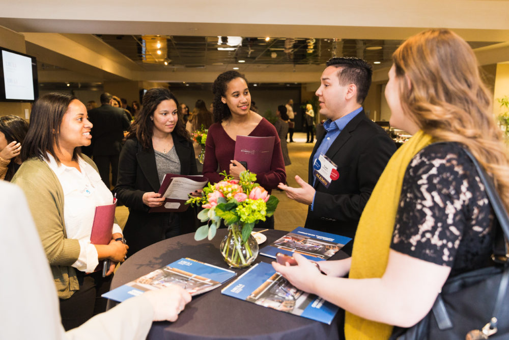 Students and alumni engaged in conversation around a table at BCLA Career Chats event