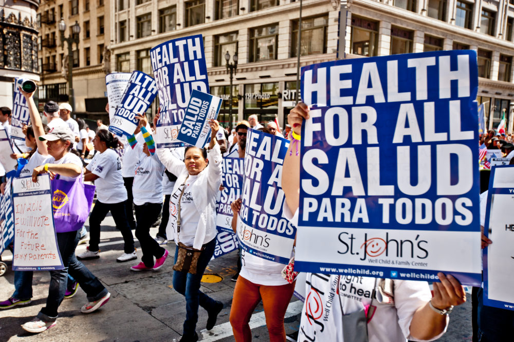Protest with participants holding health for all signs