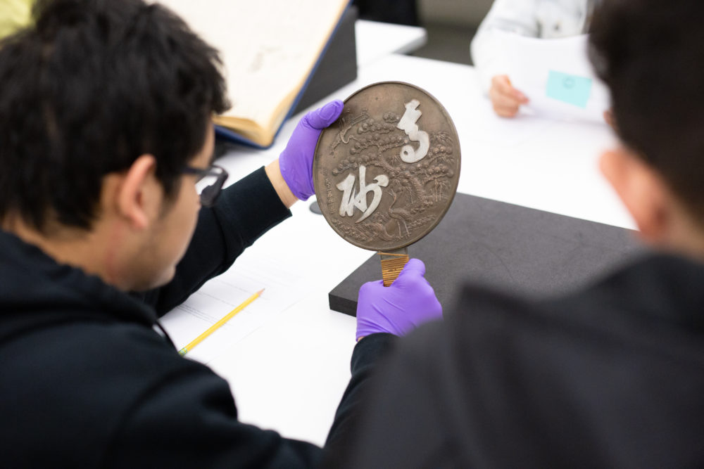 Students examine mirror from Harry Honda collection