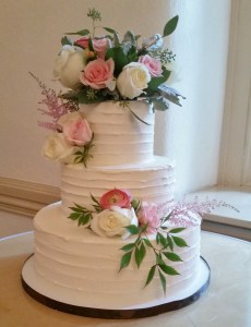 Our textured buttercream wedding cake is the perfect backdrop for fresh flowers LGBTQ