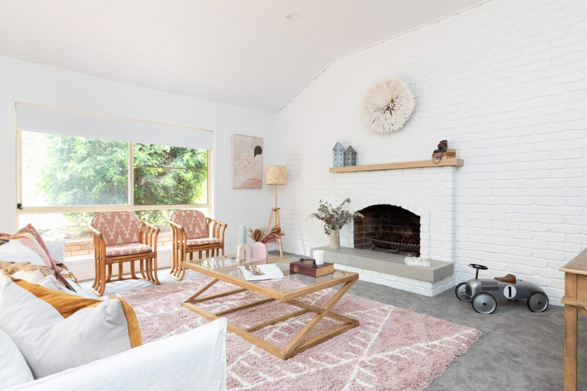White brick fireplace living room pink rug neutral