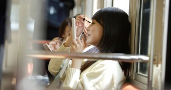Girls on the train, applying mascara