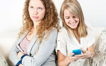 Young woman ignoring her friend checking smart phone breaching cellphone etiquette