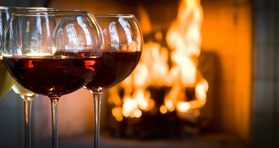 Four glasses of wine (2 red, 2 white) by a warm fire.