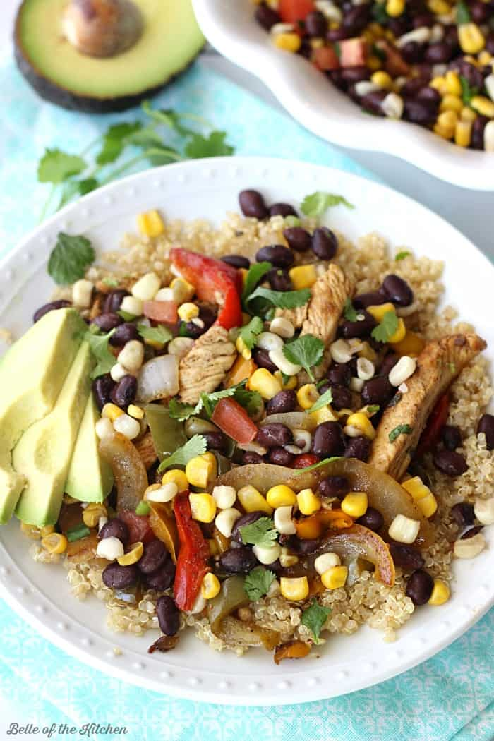 These Skillet Chicken Fajita Quinoa Bowls are made with marinated chicken, peppers, onions, and a homemade corn salsa. Serve over cooked quinoa for a healthy and delicious weeknight dinner!