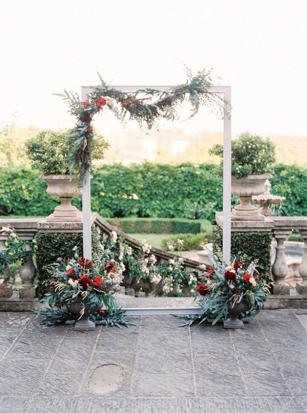 Outdoor arch and wedding ceremony with red and blue flowers and greenery - Photography: The cablookfotolab
