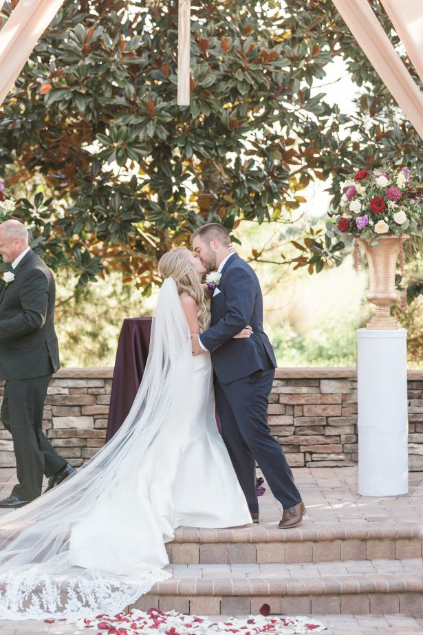 Wedding kiss at outdoor ceremony - Photography: The Hendricks