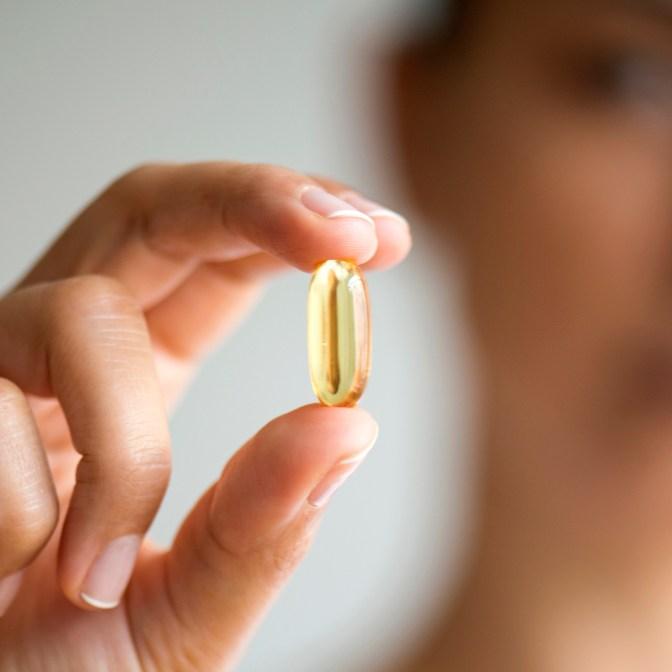 Woman holding omega 3 capsule.