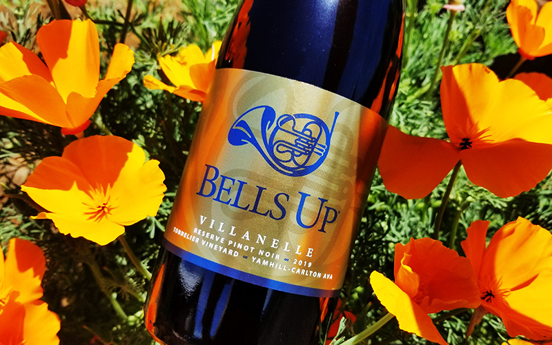 Bottle of red wine with gold label in field of poppies