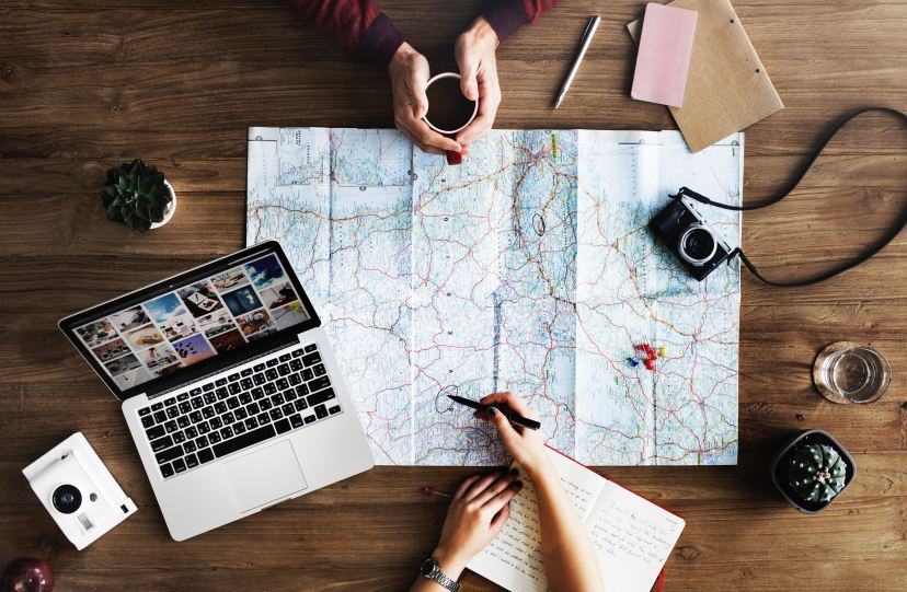 An overhead shot of two people planning a trip with a map and a laptop on a wooden surface, for first family camping trip. Photo by rawpixel on Unsplash