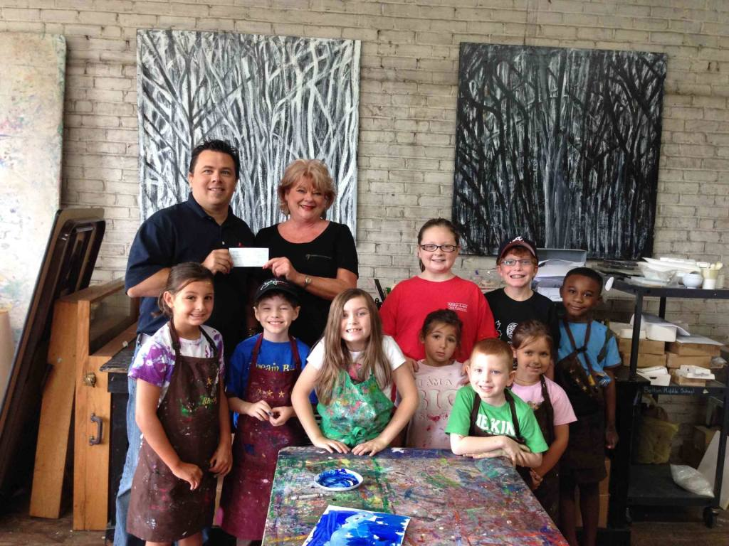 Matt Lusk presents a check from the South Carolina Chili Cookoff to Director Betsy Chapman and children