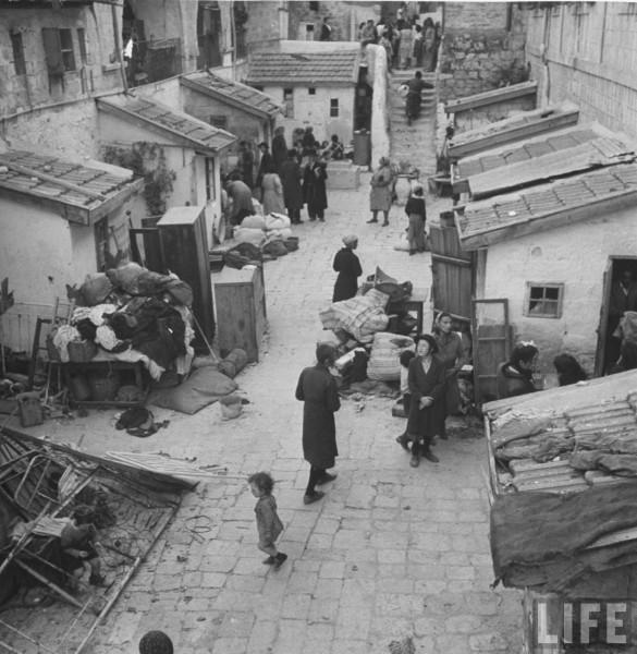 Jewish families waiting outside their homes to be evacuated by Arab troops. Jerusalem, Israel. June 1948. John Phillips