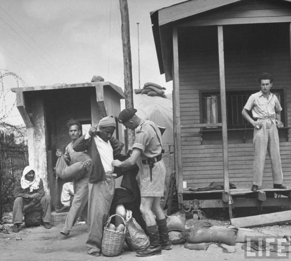 A Royal Marine searching an Arab