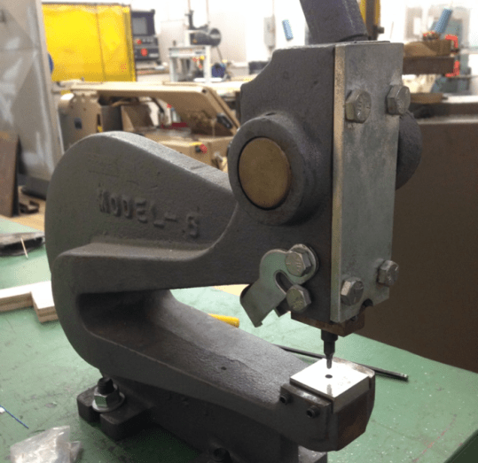 We used this hand-powered punch to hold the new tooling, letting us make teeth quickly and repeatably.