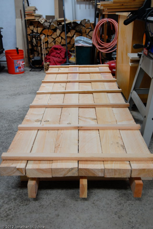 Cribbing, lumber, and stickers being laid down to start a drying stack.