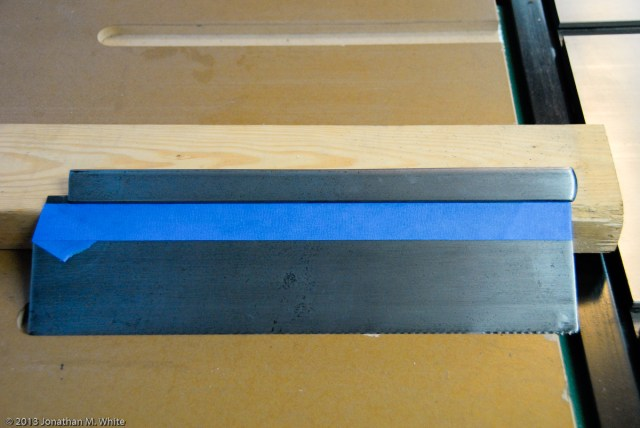 Blue painters tape is applied to mask off the saw plate before polishing the spine.