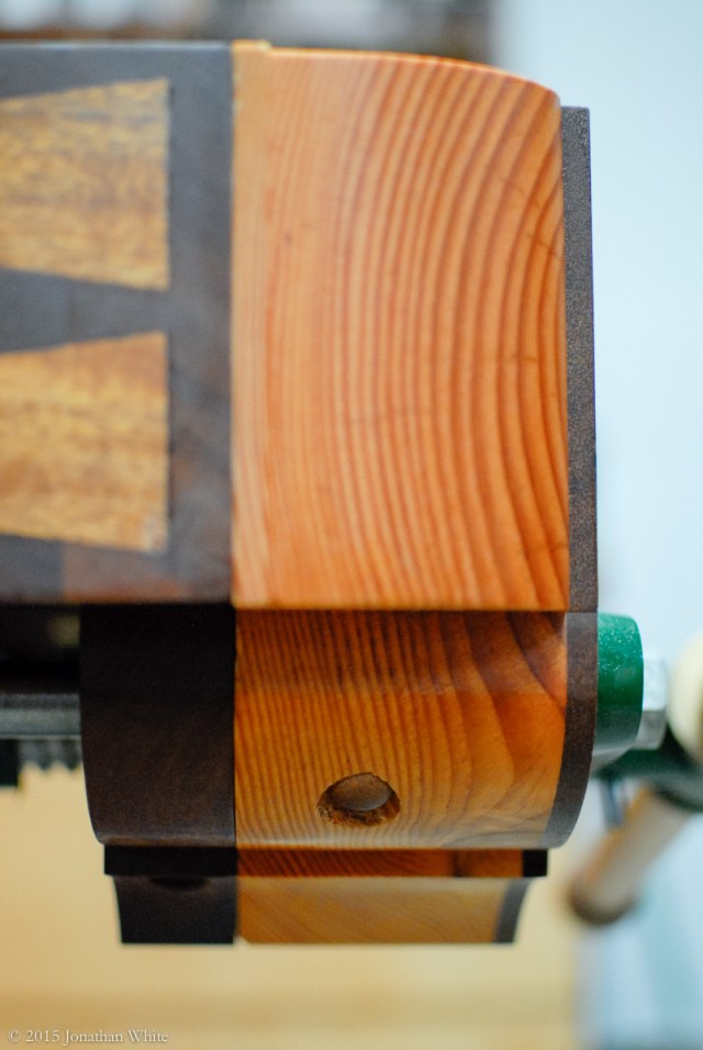 The bottom of the benchdog sits flush with the bottom of the tail vise chop when pushed down.