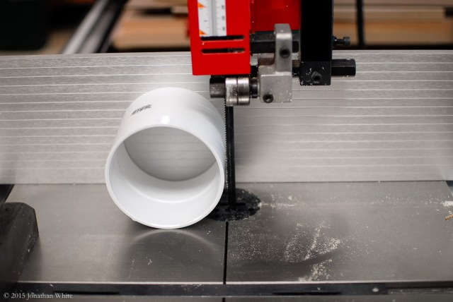 Cutting a PVC Straight Coupling in half at the bandsaw.