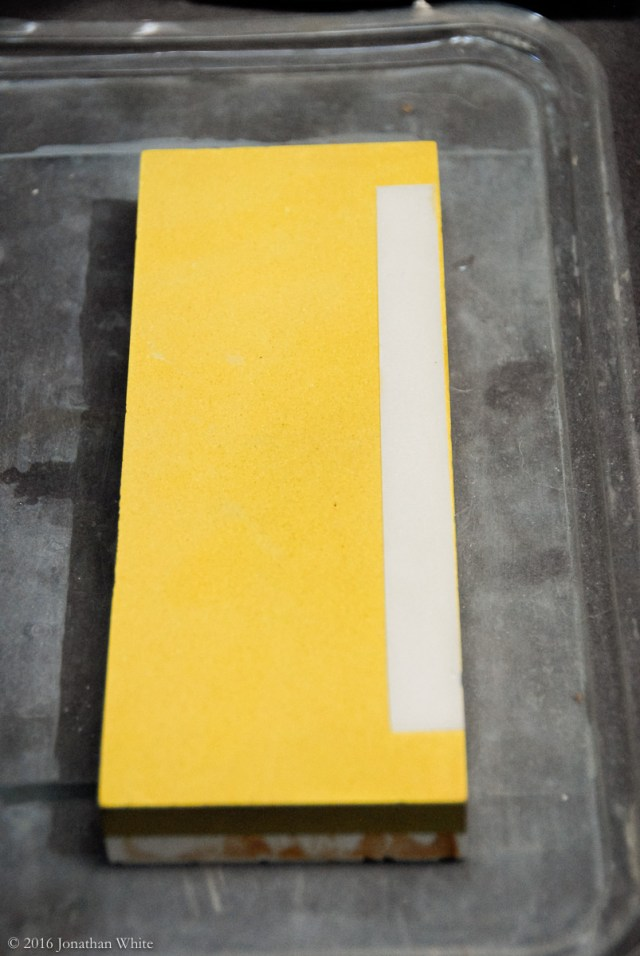 The strip is laid down one edge of the sharpening stone.