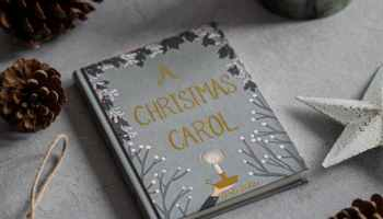 """Ding Dong Merrily on High is a Christmas Carol, and in this picture is a book with the words """"A Christmas Carol"""" on it, as well as assorted christmas decorations."""