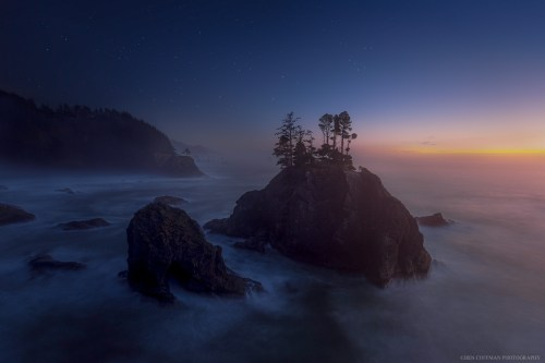 Breaking waves sound like thunder as the sun sets on a misty evening in Oregon's Samuel Boardman State Park.