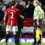 Manchester United's Neville holds back his manager Ferguson as he gestures towards referee Dean following their English Premier League soccer match in Manchester
