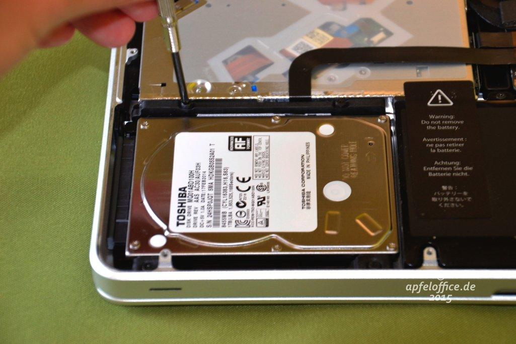 Ein Bügel hält die interne Festplatte in den Gummilagern im Macbook Pro