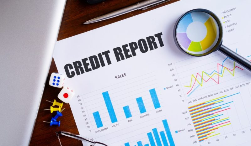 credit report text on paper sheet with magnifying glass on chart