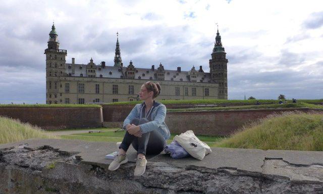 Ein Frau sitzt vor der Kronborg in Helsingør